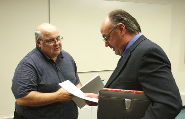 "Jenny Lancour | Daily Press Retiring Escanaba City Manager Jim O'Toole, at left, hands newly-hired City Manager Patrick Jordan a ""task list"" of on-going and unfinished projects and plans in the city following council's unanimous decision to hire Jordan during a special meeting at city hall Tuesday."