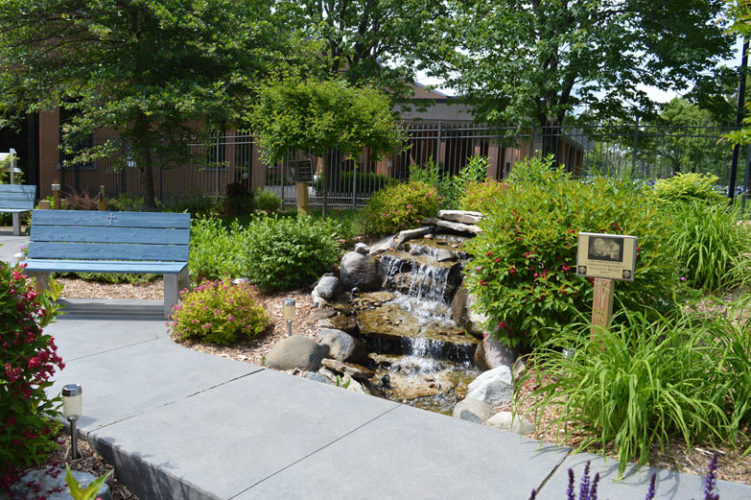 Haley Gustafson | Daily Press  The vanishing waterfall feature in OSF's Serenity Garden flows steadily Tuesday afternoon. The Serenity Garden, located outside of OSF St. Francis Hospital in Escanaba, is a community garden maintained by the Masters Gardeners Association and other area volunteers.