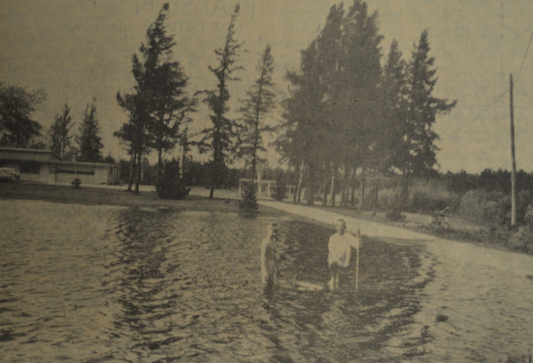 """Daily Press photo Equipped with skin diving mask and a small wooden raft, Bobby Bosk, left, and Billy Cretens take a swim in a most unlikely place, the front yard of the William Stewart residence on the Jaeger Road. The """"pond"""" was created by several days of heavy rain in 1966."""