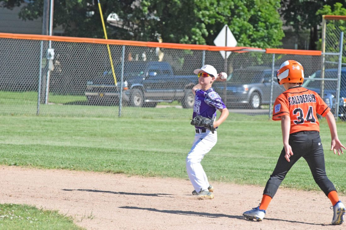 Gladstone shortstop Gavin Frossard gets ready to fire th­e ball to first base as Escanaba runner Alex Stalboeger looks on in Friday's District 10 Little League Minor Boys All-Stars game at Dickson Field.