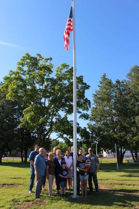 Courtesy Photo  Members of Ed Blahnik's family stand by the flag pole that was placed in his honor at Bark River's downtown park on the Fourth of July.