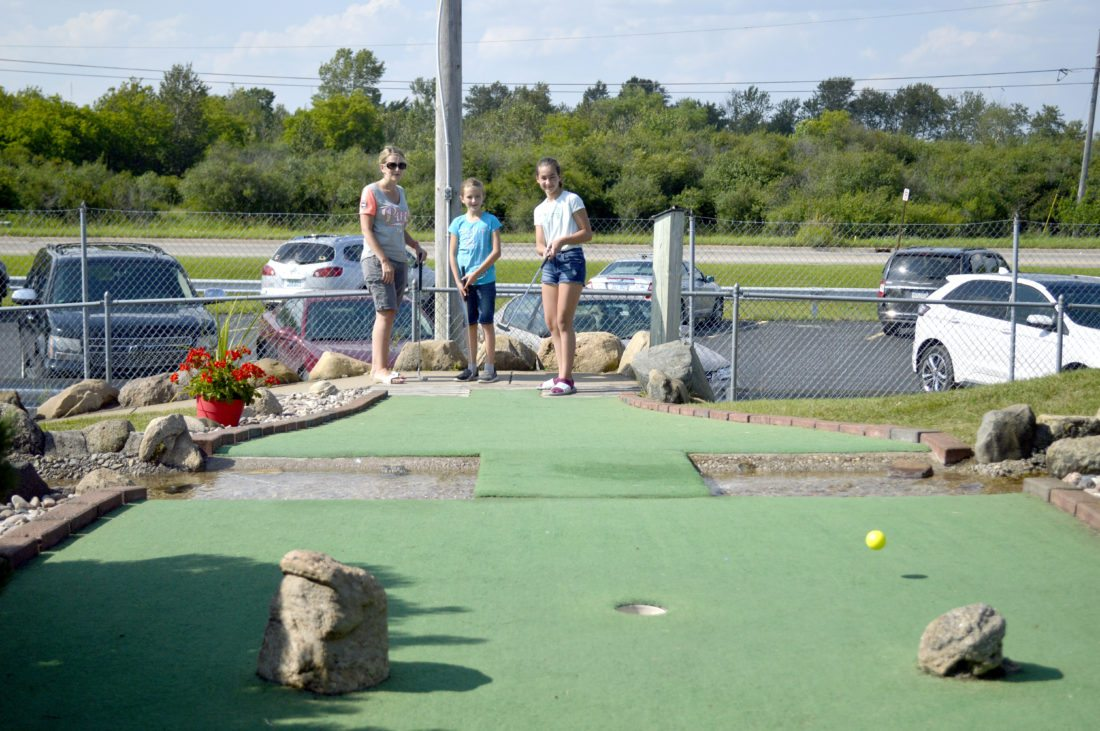 Ilsa Matthes | Daily Press Tara Weaver and her daughter Sophia watch as Sophia's cousin, Zoe Wilson expertly avoids a water feature and drops her ball on the green of hole two during the 10th Annual United Way of Delta County Mini Golf Tournament at the Escanaba Family Fun Park Thursday. In total, 111 people took part in the tournament, which raised money for Dolly Parton's Imagination Library. The tournament's first-place team, Kendrick King and Tony Scott, had a score of 49. For individual golfers, Calvin Sinclair had the top score for golfers aged 10 and under with a score of 52, Tanner Howes had the top score for golfers aged 11-14 with a score of 50, Sean Sailer had the top score for golfers aged 15-18 with a score of 52, and Jennie Gylock had the top score for golfers aged 19 and older with a score of 46.