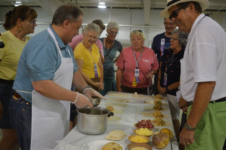 Haley Gustafson | Daily Press  At left, Brad Mantela, owner of Dobber's Pasties in Escanaba, discusses how a pasty is made fresh daily at his shop while a crowd of Wally Byam Caravan Club International (WBCCI) members look on Tuesday at the Ruth Butler building on the Upper Peninsula State Fairgrounds in Escanaba. The WBCCI is celebrating its 60th Airstream rally this week at the fairgrounds. As part of the week's activities, Mantela talked about the history of the pasty, as well as showing rally attendees how to make the iconic meat pies.