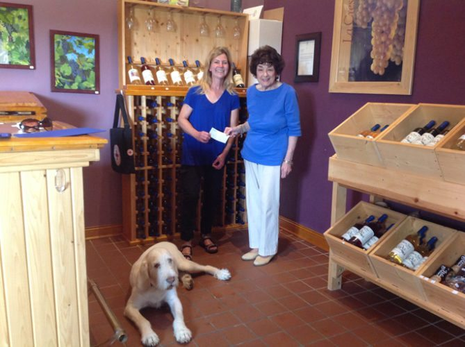 Courtesy photo Susan Anthony of Northern Sun Winery, left, presents a check to AAUW member Kathleen Bennett  for $300, while Smitty, the winery dog, looks on.