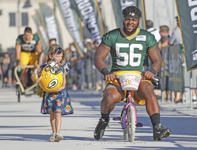 AP photo Linebacker Johnathan Calvin rides a bike to NFL football training camp Thursday in Green Bay.