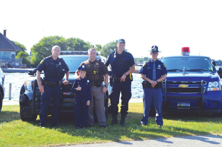 Haley Gustafson | Daily Press  Local law enforcement officers pose for a photo with youngster Carter Millette (wearing a police officer costume), second from left, during the Back our Blue event held at the Municipal Dock in Escanaba Wednesday evening. The second annual event was held to show support and appreciation for local law enforcement officers. Officers shown, from left, are Gladstone Public Safety Officer Mike Willemsen, Millette, Delta County Sheriff's Department Deputy Tom Lewis, Michigan State Police K-9 Team Officer Scott Kelley, and Michigan State Police Trooper Tyler Vargo.