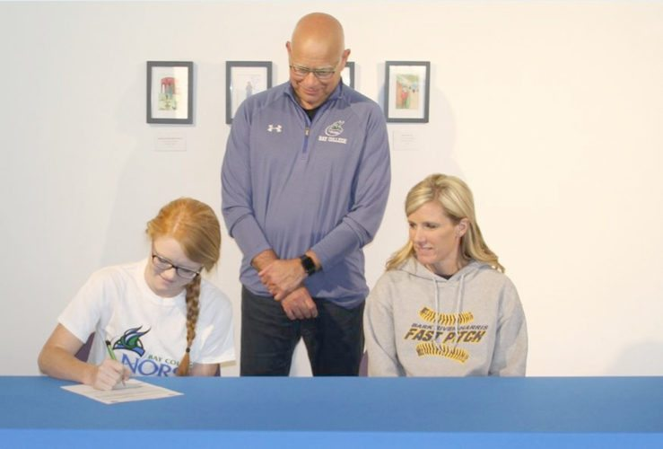 Courtesy photo Bark River-Harris' Paige Welch signs a national letter-of-intent to attend Bay College and compete on the women's basketball team. Welch's mother Vicki Welch and Bay coach Rae Drake Jr. look on during the signing. Welch is one of four recent signings for the Norse.