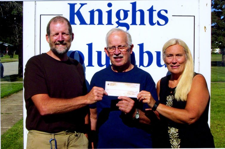 Courtesy photo Above, Allan Blahnik, center, Tootsie Roll Drive co-chair, presents donations to, left, Gus and Chris Olson, of CHAT (Community Handicap Awareness Team).