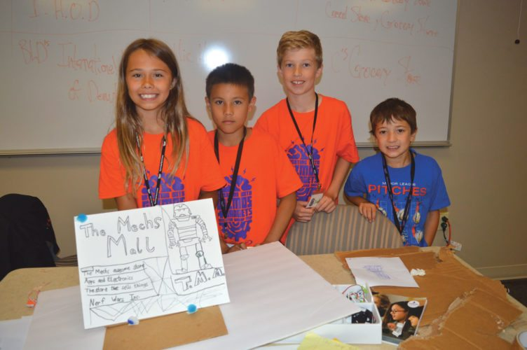 """Jordan Beck   Daily Press """"The Mechs"""" — from left, Haylee Gatien, Justin Bergquist, Jack Peterson, and Caden Malone — show off a sign they made as part of a project for modular electronics day camp """"Inventing With Gizmos and Gadgets."""""""