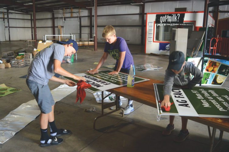 Haley Gustafson   Daily Press  From left, Andrew, Avery, and Mayce Hanson clean poster boards in the Miracle of Life Building located on the Upper Peninsula State Fairgrounds in Escanaba Tuesday. Over the the past few weeks, the fairgrounds has been bustling with activity as volunteers and maintenance crews prepare for the U.P. State Fair, which begins Monday.