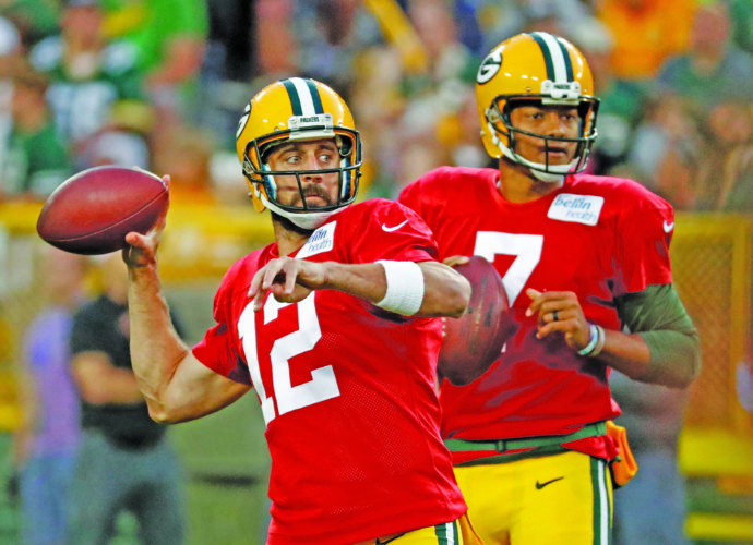 AP photo Green Bay quarterback Aaron Rodgers, left, and Brett Hundley throw passes during an NFL football training camp practice in Green Bay.