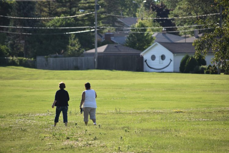 Jon Brines/The Journal Times via AP In this undated photo a couple walk near a garage in Racine, Wis. The smiley face they painted on the back of the garage in 2014 faces Lockwood Park.