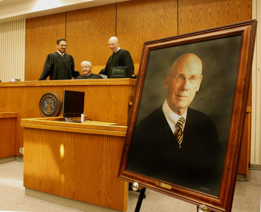 Jenny Lancour | Daily Press A portrait of Judge Stephen Davis, who retired nearly eight months ago, is displayed following a ceremony in Delta County Circuit Court on Wednesday while Davis, standing at right, poses for a photograph with current Judge John Economopoulos, standing at left, and retired Judge Dean Shipman, seated.