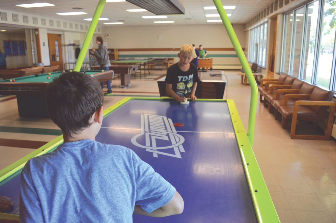 Jordan Beck | Daily Press Escanaba Upper Elementary School fifth-grade students Xander Blomstrom, left, and Patrick Gentry face off in a round of air hockey in the Catherine Bonifas Civic Center's game room Monday.