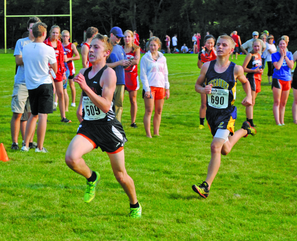 Burt Angeli/The Daily News Photos Escanaba's Justin Sanpaka, left, and Negaunee's Eric Anderson race to the finish line in a battle for fourth place. Sanpaka finished fourth in 18:20.1, followed by Anderson in 18:21.6.