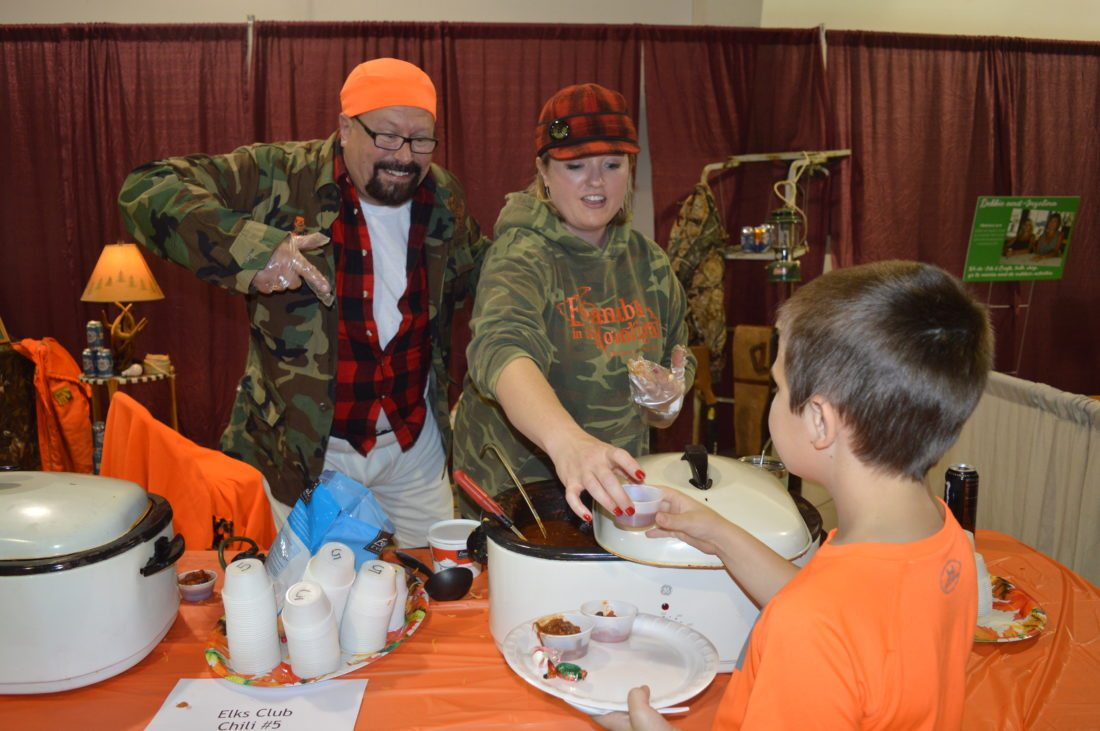 "Jordan Beck | Daily Press From right, Escanaba Upper Elementary School fourth-grader Noah Bizeau takes a cup of chili from Sara LaMarch as Jack Willette looks on at the Soup'r Chili Challenge Tuesday. Bizeau said his favorite part of this event was ""getting tons of chili and soup."""
