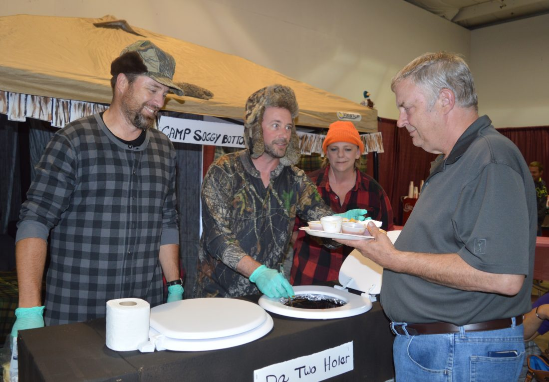"Jordan Beck | Daily Press From left, Bay Pines Center Chefs Tom Wetthuhn and Matt Wiles, along with Bay Pines Center Youth Specialist Becky Barnhart, serve Wayne Johnson a cup of chili at the Soup'r Chili Challenge Tuesday. The center's booth, ""Camp Soggy Bottom,"" won the People's Choice Award for best booth display."