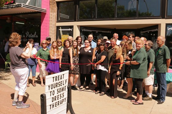 Courtesy photo Jody Bugay, center, owner of Dress Up in downtown Escanaba, cuts the ribbon during the store's grand opening recently.