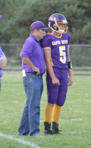 Avery Bundgaard | Daily Press Rapid River coach Steve Ostrenga talks with his quarterback Brent Lundquist before a play Friday against Ontonagon at Rapid River.