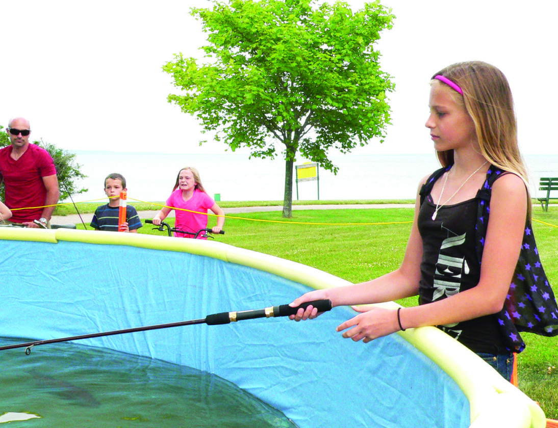 Jordan Beck | Daily Press Above, young angler Dasia Dubord tests the waters at the Bay de Noc Great Lakes Sports Fisherman's Fish Pond at Escanaba's Rock the Dock event, held at the municipal dock.