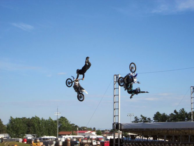 Patricia VanEnkevort | Daily Press  Scott Murray, left, and a fellow motocross rider catch some air during a performance at the Upper Peninsula State Fair last year. Murray and a team of professional riders will be returning to the fairgrounds Saturday. The show will begin at 7:30 p.m.