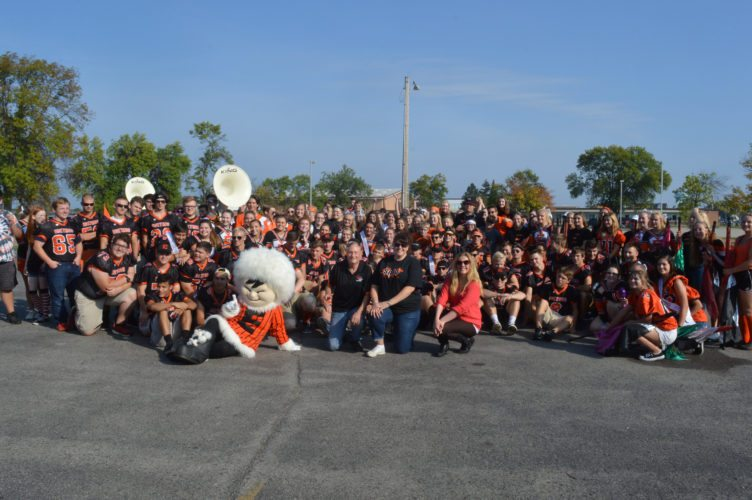 """Haley Gustafson   Daily Press  The Escanaba Eskymo football team, Christian Park Healthcare staff, Escanaba cheerleaders, marching band, and school mascot, """"Mo"""" pose for a group photo during a pep rally held at Christian Park Healthcare Center in Escanaba Friday."""