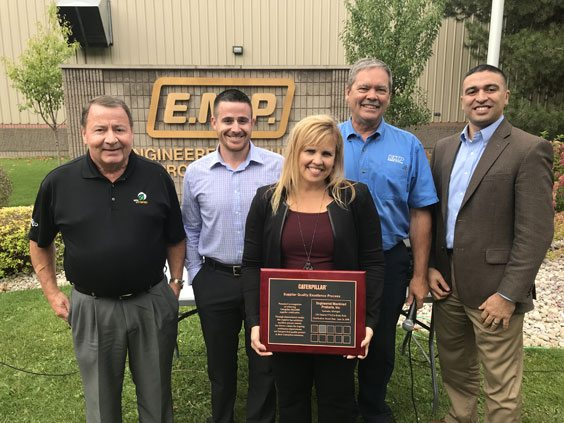 Courtesy photo Caterpillar Inc. recently announced that Engineered Machined Products (EMP) of Escanaba has been awarded the Caterpillar Platinum Certification, and new precision machining business. Shown during an award presentation are, from left, Brian Larche, Brandon Larche, Tammy Wolfe-Beauchamp and Bruce Jacobson of EMP and Ernie Reyes of Caterpillar.