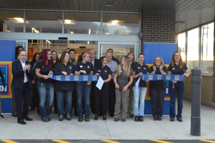 Haley Gustafson | Daily Press  Local dignitaries and ALDI, Inc. representatives cut a ribbon during the grand opening ceremony for the new ALDI grocery store in Escanaba this morning. The Escanaba location of the grocery store chain is the first to open its doors in the Upper Peninsula. Shown in front from left are, ALDI District Manager Bob Best, ALDI employees Nina Kidd, Katie Whitmer, Brittany Judson, Cassie Franti, Escanaba ALDI Store Manager Avery Hendrickson, ALDI employees Stephanie Westerberg, Janice Schimmepenny, and Kim Paquette. Shown in back from left are Bay College representative Jill Martin, Escanaba City Council Member Mike Sattem, Publisher of the Daily Press Corky DeRoeck, Escanaba City Council Member Ralph Blaiser, and ALDI employee Julie Matecki.