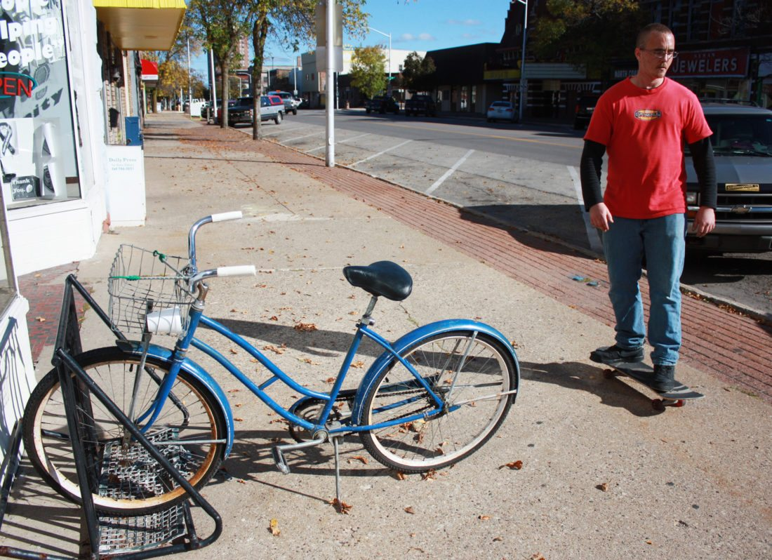 Jenny Lancour | Daily Press Ron Micheau, of Escanaba, rides his skateboard in downtown Escanaba while passing a bicycle in a bike rack Wednesday afternoon.