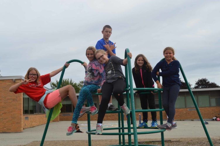 Haley Gustafson | Daily Press  J.T. Jones Elementary School students pause from playing on playground equipment at their school in Gladstone Monday afternoon. Shown, from left, in front, are Alicia Meyer, Daizee Wheaton, and Bre Ketcham, Anna Kevsquve, Kensley Chamberlain, and Mason Peltin (in back).