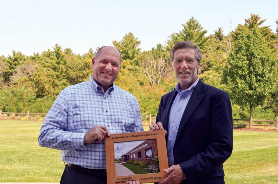 Courtesy photo Tom Harrell, CEO of the Alger Delta Cooperative Electric Association, left, receives a token of esteem from Mike Peters, president and CEO of WPPI Energy.