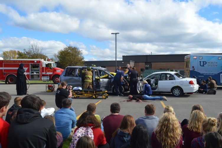 "Jordan Beck | Daily Press Local law enforcement agencies respond to a mock car crash in the Delta-Schoolcraft ISD parking lot Wednesday. This was part of ""Every 15 Minutes,"" a program designed to teach Escanaba Area High School students about the risks associated with driving while drunk or otherwise impaired."