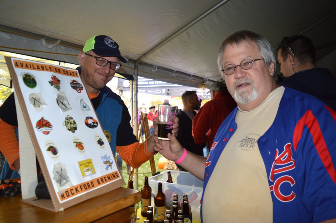 Jordan Beck | Daily Press From left, Mark Ostrander of Rockford Brewing Company hands a beer to Madison, Wis. resident Steve Nelson during the 12th annual UPtoberfest Saturday. According to Bay de Noc Brewers, the local homebrewing group which hosted the event, tickets for this year's UPtoberfest sold out faster than ever before.