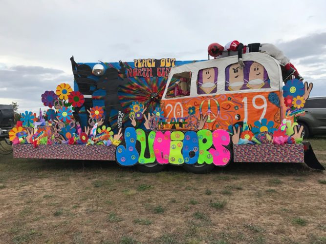 "Haley Gustafson | Daily Press  The Rapid River High School junior float is shown during their homecoming events Friday. This float displayed the saying ""Peace Out North Central"" with flowers, peace signs, and a fully lit colored disco ball. The theme for this year's homecoming was 70s Hippie ""Groovy Baby."""