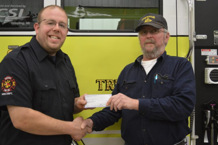 Haley Gustafson | Daily Press  At left, Escanaba Township Volunteer Fire Department Chief Matt Rian accepts a donation of $700 from Terry Plouff, president of the U.P. Garden Tractor Club, at the John D. Besse Fire Station recently.