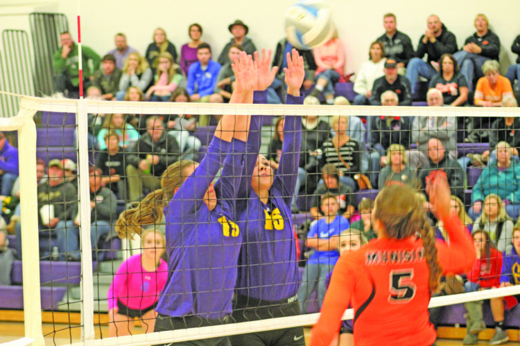 Avery Bundgaard | Daily Press Rapid River's Shelby LaCosse (19) and Aleece Paulin (15) go up for a block of a ball hit by Munising's Kianne Wendt (5) Thursday during the Class D district final at Rapid River.