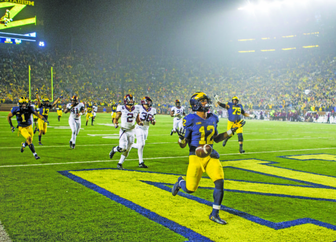AP photo Michigan running back Chris Evans (12) celebrates in the end zone after scoring a TD against Minnesota Saturday in Ann Arbor.