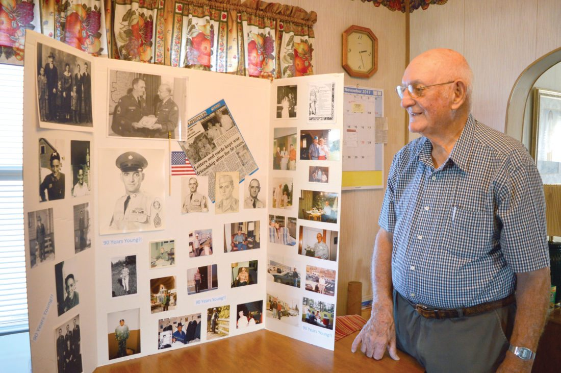 Jordan Beck | Daily Press Escanaba resident and World War II veteran John D'Antonio looks at a collection of photos taken throughout his life. D'Antonio celebrated his 50th year of retirement from the military earlier this year