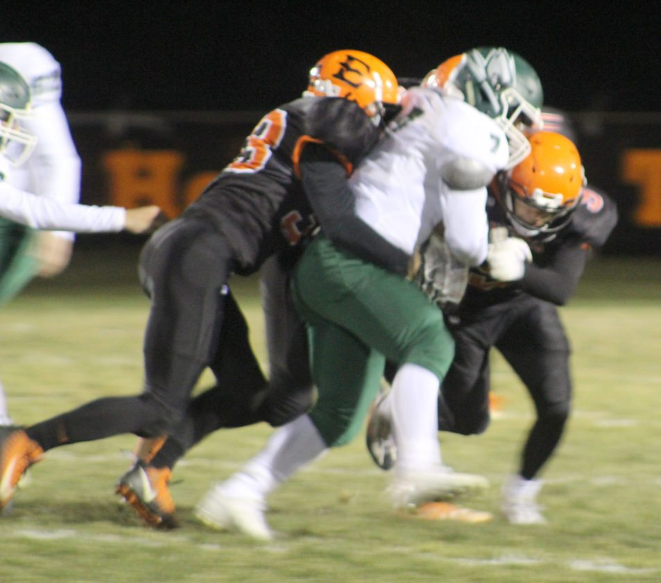 Avery Bundgaard | Daily Press Escanaba's Tyler Cook (left) and Hayden Haslow (right) tackle Williamston's Evan Field Friday during the Division 4 regional final at Escanaba.