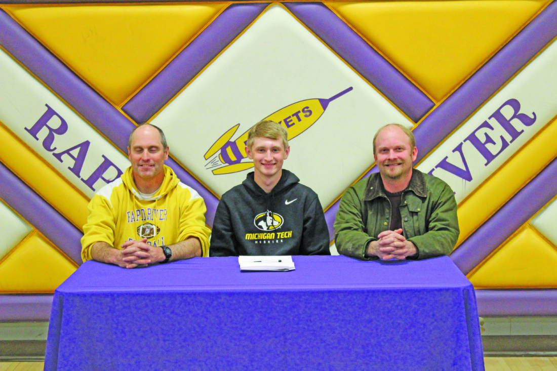 Avery Bundgaard | Daily Press Rapid River's Luke Gustafson (center) signed a letter of intent Friday to attend Michigan Tech and compete for the men's track and field team in the pole vault. Pictured with Gustafson are Rapid River track and field coach Steve Ostrenga (left) and Rapid River pole vault coach Mark Christoff (right).