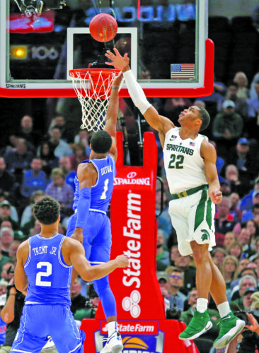 AP photo Michigan State guard Miles Bridges (22) blocks the shot of Duke guard Trevon Duval (1) during first-half action Tuesday in Chicago.  No. 4 Kansas topped No. 7 Kentucky 65-61 in the second game.