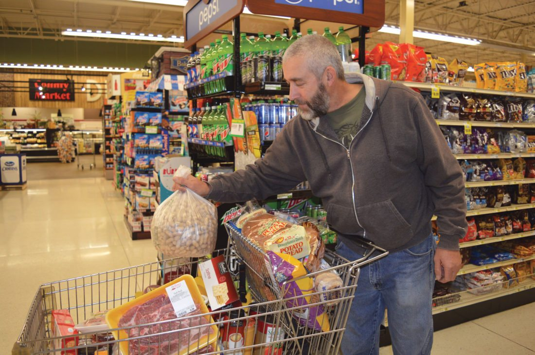 Jordan Beck | Daily Press Munising hunter Bryan Ekberg fills a cart at Elmer's County Market Monday while getting ready for Michigan's firearm deer season. Popular items at Elmer's during this season include beer, eggs, butter, sausage, bacon, smoked oysters, pickled eggs, and sardines.