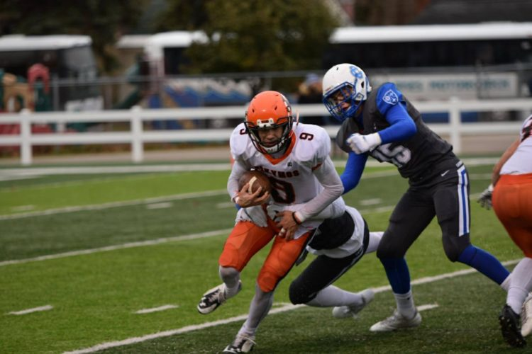 Courtesy photo Anne Truitt Escanaba's Hayden Haslow (9) fights for yardage against Grand Rapids Catholic Central defenders in Saturday's Division 4 state semifinal game in Traverse City.