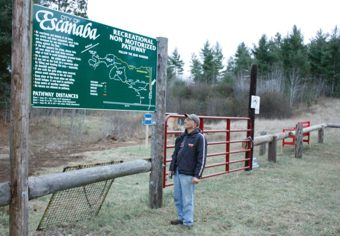 Jenny Lancour | Daily Press Escanaba resident Mike Segorski checks out the ski hill parking lot which has recently undergone several improvements including fencing made from old telephone poles, a bench received from the county's probation department, and landscaping.