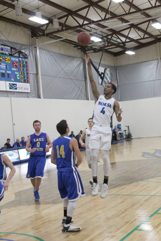 Avery Bundgaard | Daily Press Bay College's Alfonzo Fields (4) puts up a floater over Lake Superior State's Jacob Holzhei (14) during the first half Monday at Bay College.