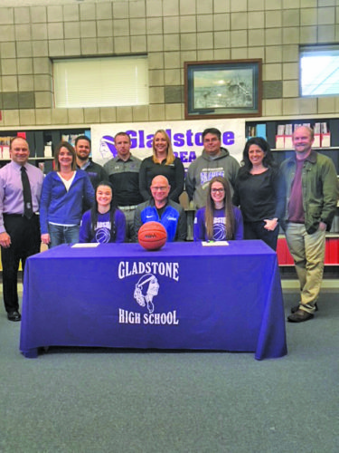 Gladstone's Taylor Hunter and Kaitlyn Hardwick signed a national letter of intent to attend Bay College and play basketball for the Norse. Pictured at the signing in front row from left are: Hunter, Bay College women's coach Rae Drake Jr. and Hardwick. In back row from left are: Darrin and Angie Hunter, Gladstone athletic director Andy Jacques, coach Andy Cretens, Bay assistant coach Katie Poma, Duane Hardwick and Cristine and Mark Christoff.