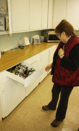 Jenny Lancour | Daily Press Brenda Norden, head cook at the senior center in Rock, demonstrates the difficulties in opening the drawers in the kitchen at the Maple Ridge Township Hall earlier this week. The township is raising funds to pay for renovations in the out-dated kitchen including replacing the cabinets, sinks and ceiling
