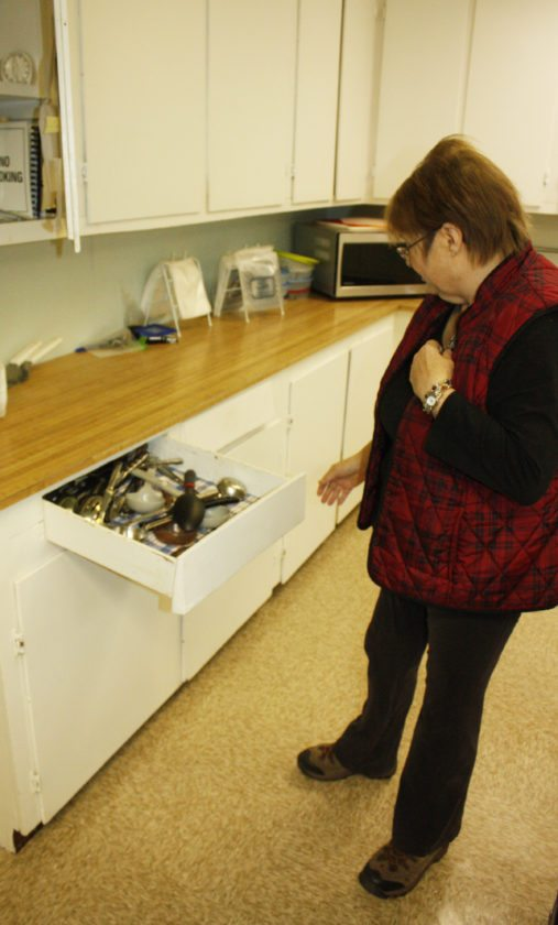 Jenny Lancour   Daily Press Brenda Norden, head cook at the senior center in Rock, demonstrates the difficulties in opening the drawers in the kitchen at the Maple Ridge Township Hall earlier this week. The township is raising funds to pay for renovations in the out-dated kitchen including replacing the cabinets, sinks and ceiling