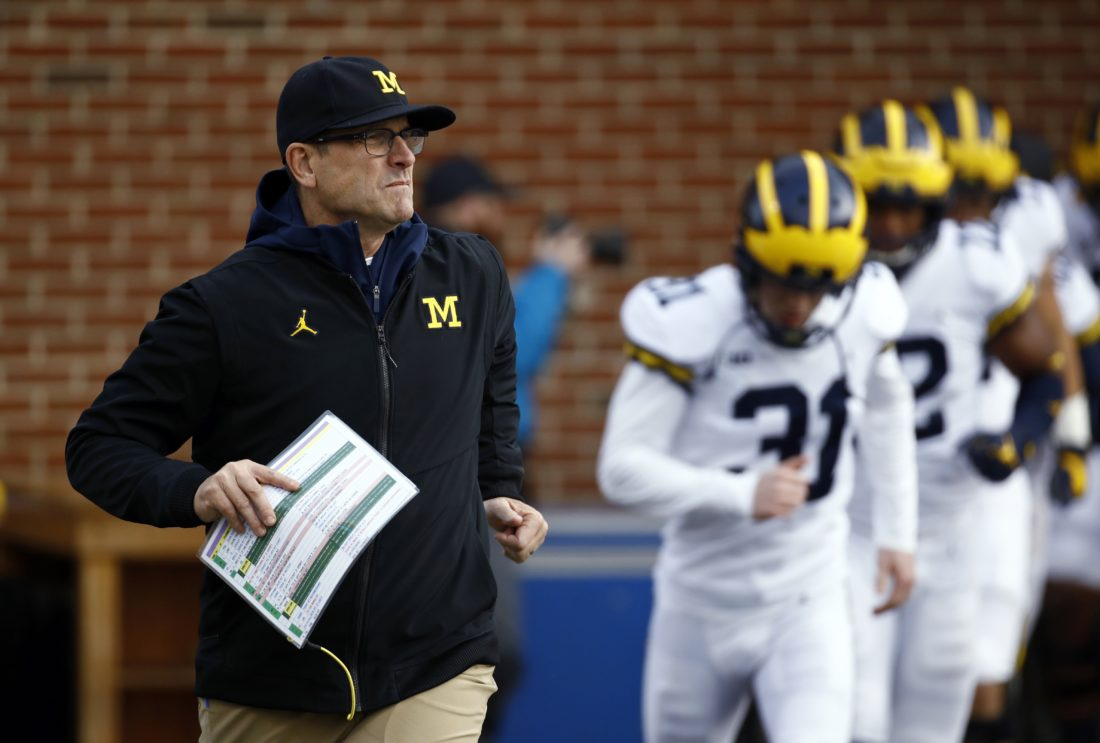 AP photo Michigan coach Jim Harbaugh runs onto the field with his team before a game against Maryland in College Park, Md.