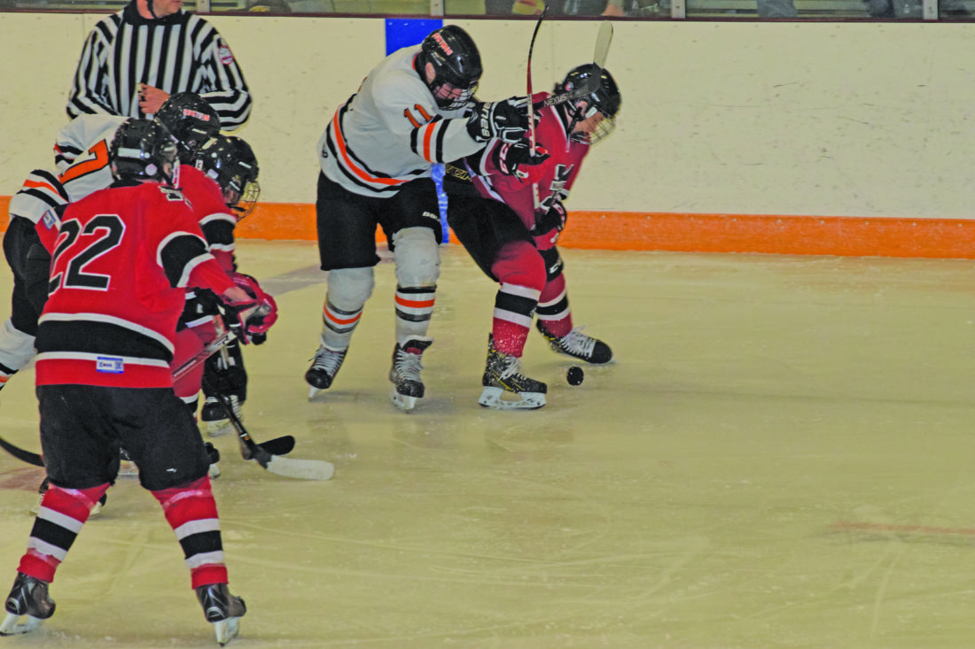 Mike Mattson   Daily Press Escanaba's Aaron Young (11) and Marquette's Ethan Silverstone battle for the puck after a faceoff in Tuesday's season opener for the Eskymos.